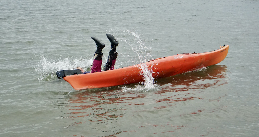 Person tipping over in a sea kayak
